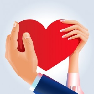 Male and female hands holding big red heart